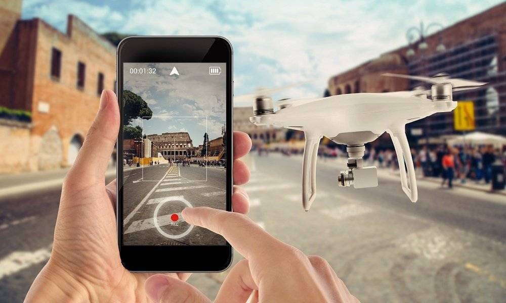 Smart phone control drone with app. City street in background.